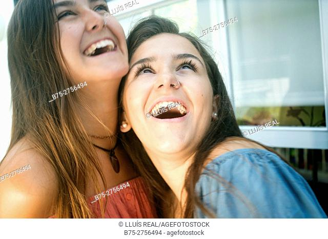Two happy teenagers laughing