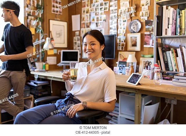 Portrait smiling, confident creative businesswoman drinking tea in office