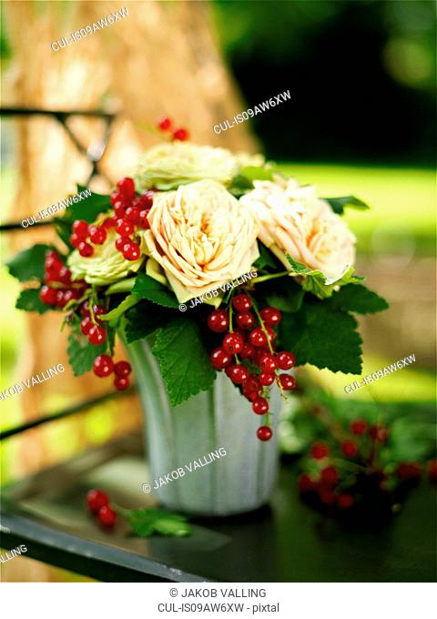 Flower arrangement of roses and redcurrants on garden table