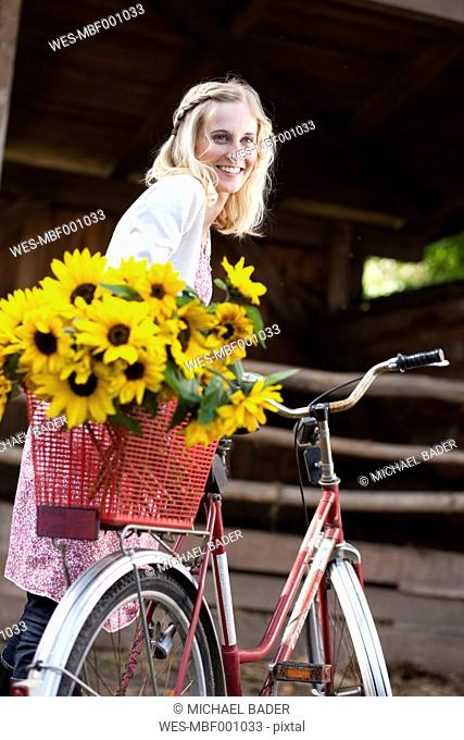 Germany, Saxony, Young woman looking away and smiling