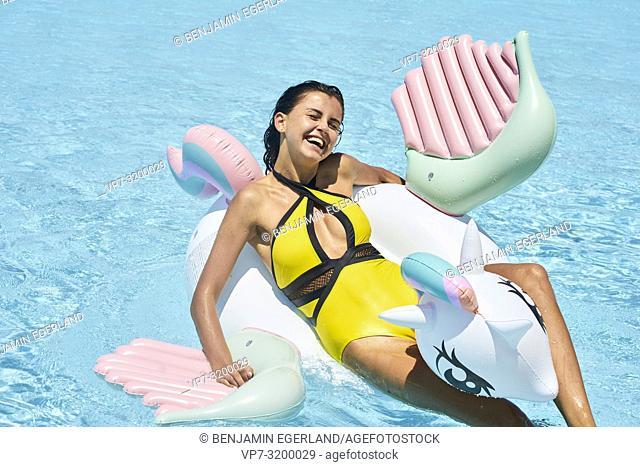 woman on inflatable, summer, pool, bikini, holiday, happy, laughing, fun, sexy, bikini