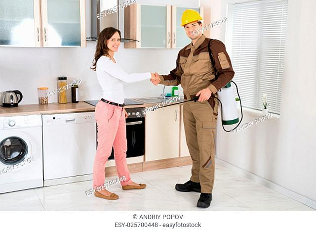 Happy Woman And Young Pest Control Worker Shaking Hands To Each Other In Kitchen Room