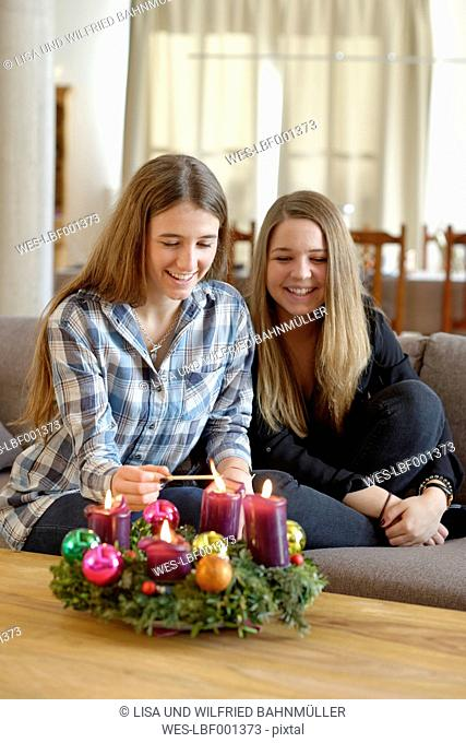 Young woman lighting candle on Advent wreath while her friend is watching