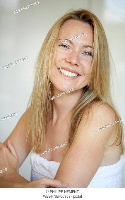 Portrait of a smiling woman, wrapped in towel