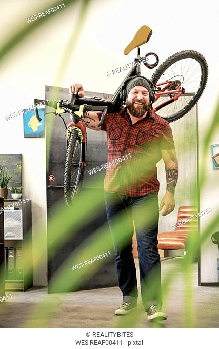 Happy man wearing headphones carrying bicycle in office