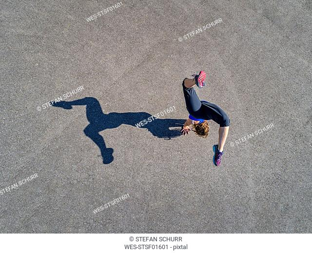 Aerial view of sportive young woman training handstand