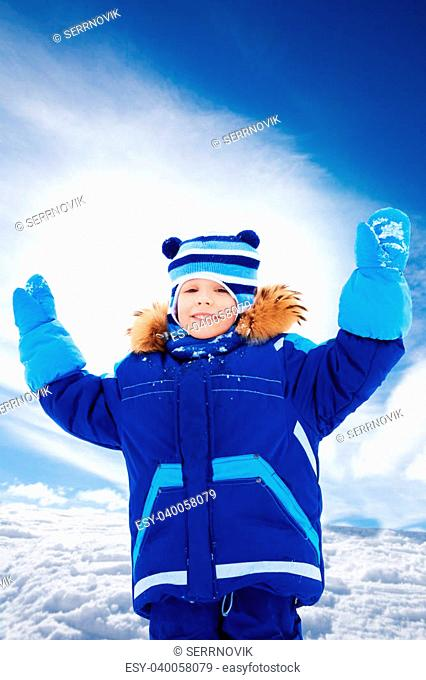 Portrait of happy boy standing with lifted from excitement hands on snow outside in winter