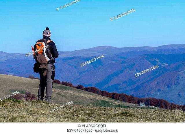 Happy young man standing on mountain. Happy young tourist man with backpack standing on rocky cliff and enjoying panoramic view over afforested mountains