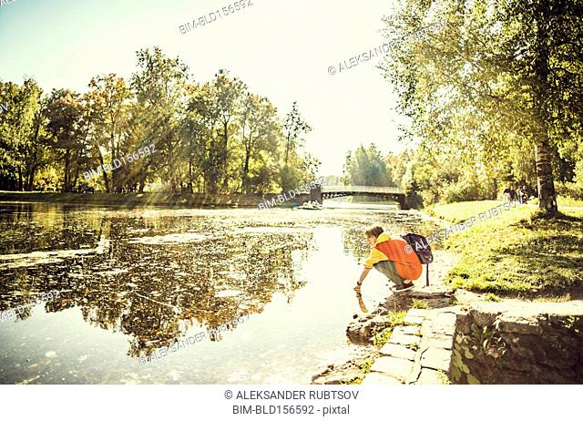 Caucasian woman dipping hand in park pond