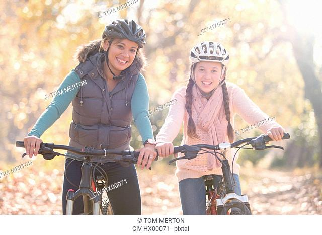 Portrait of smiling mother and daughter on mountain bikes in woods