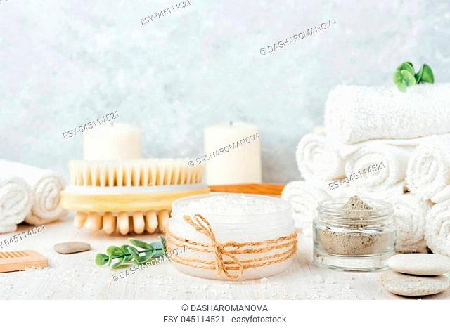Sea salt, white rolled towels, candles, green herbs, natural clay mask for face and body