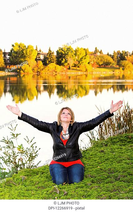 Mature woman with arms raised in worship beside lake in autumn; Edmonton, Alberta, Canada