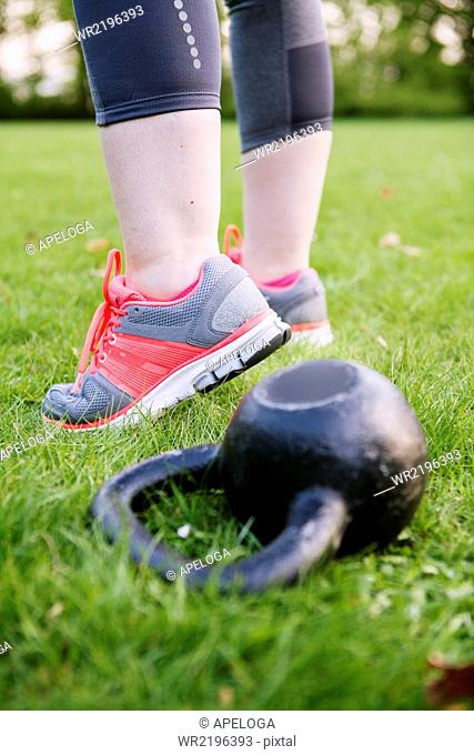 Low section of woman standing by kettlebell at grassy field
