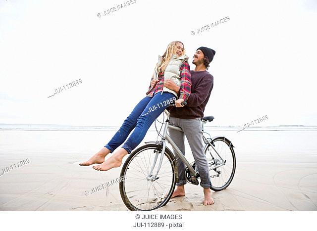 Boyfriend with bicycle hugging girlfriend on handlebars on beach