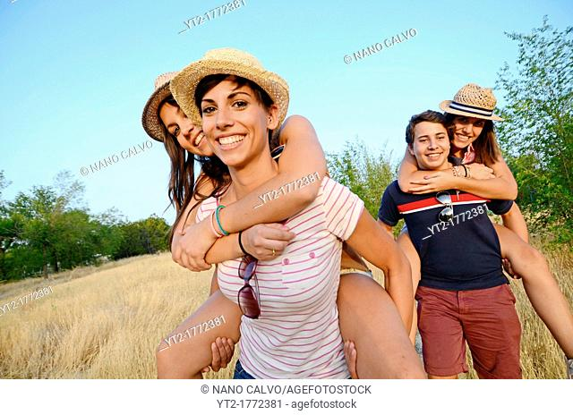 Young group of three women and a man play in nature