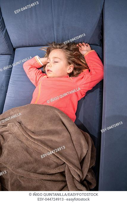 above view of blonde caucasian five years old child, lying on her back on blue sofa, sleeping pleasantly with arms up and covered with a blanket