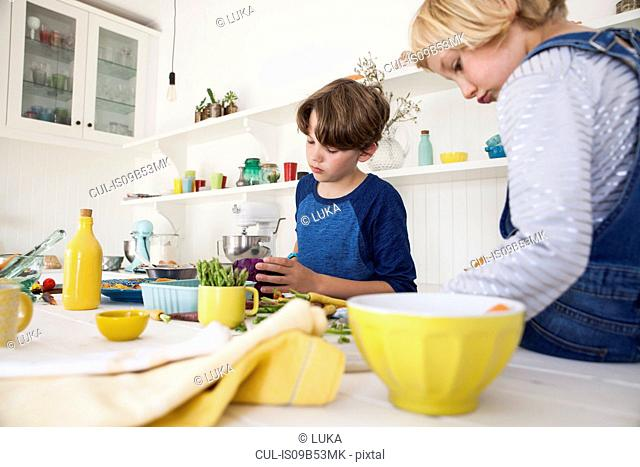 Girl and brother preparing fresh vegetables at kitchen table