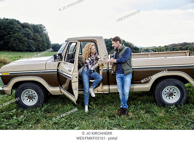 Couple at pick up truck with beer bottles