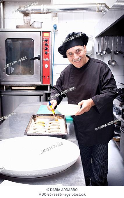 Argentine chef Pascual Juliano of Roman restaurant La Caletta preparing empanadas (the same he prepared for Pope Francis) brushing them with the red of an egg...