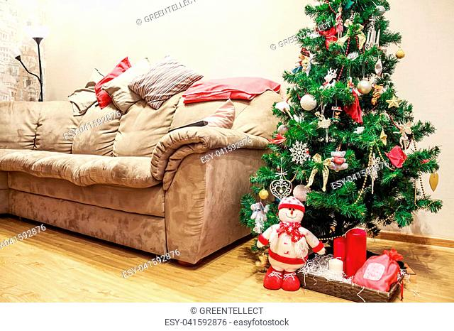 Christmas background. Interior room decorated in xmas style with new year tree and beige sofa