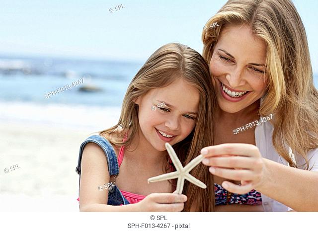 MODEL RELEASED. Mother with daughter holding a starfish
