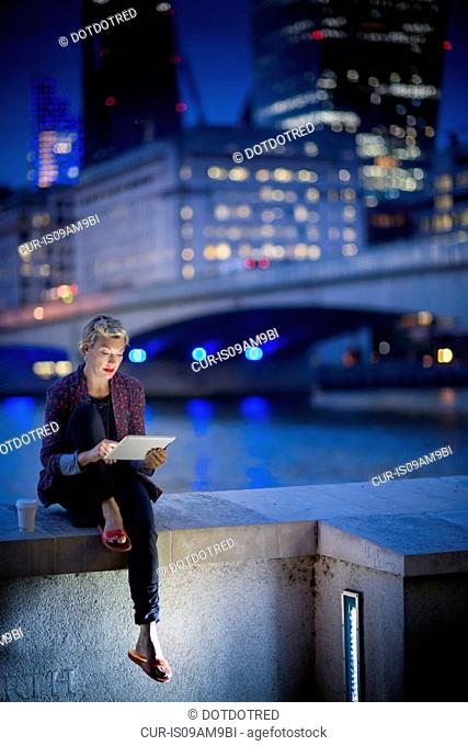 Mature businesswoman on Thames waterfront using touchscreen on digital tablet at night, London, UK