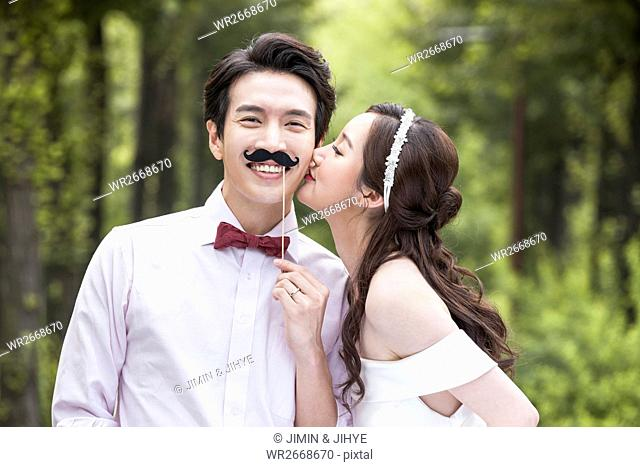 Portrait of young romantic wedding couple outdoors