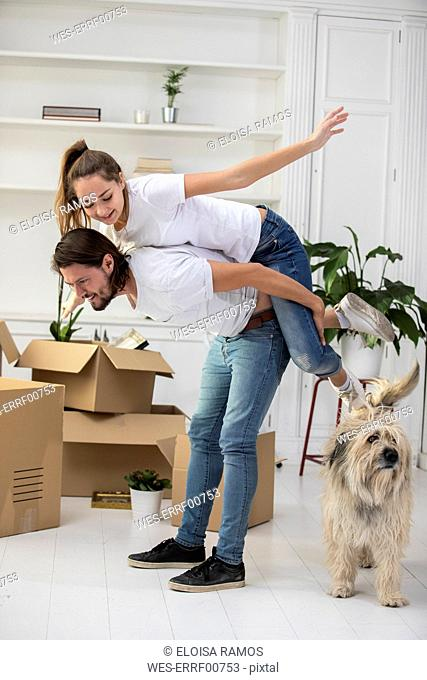 Happy couple with dog and cardboard boxes in new home