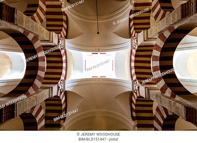 Low angle view of ornate arches and skylights in mosque, Cordoba, Andalusia, Spain
