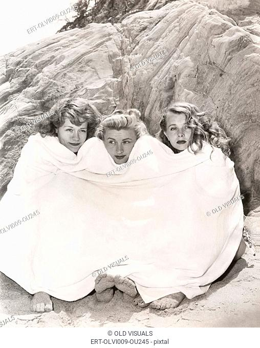 Three women huddled under a towel on beach