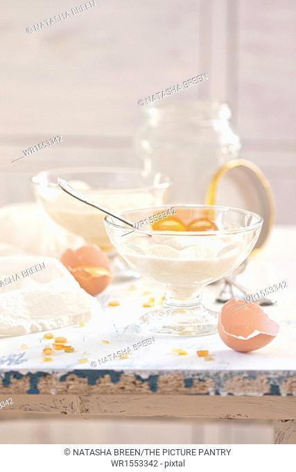 Honey mousse dessert in glass vase on white wooden table