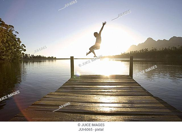 Man jumping from jetty into lake at sunset, rear view lens flare, backlit