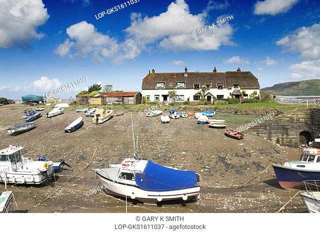 England, Somerset, Porlock Weir. Thatched coastal cottages and boats at the small tidal harbour of Porlock Weir