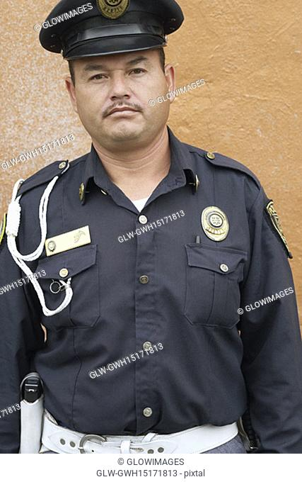 Portrait of a police officer standing in front of a wall