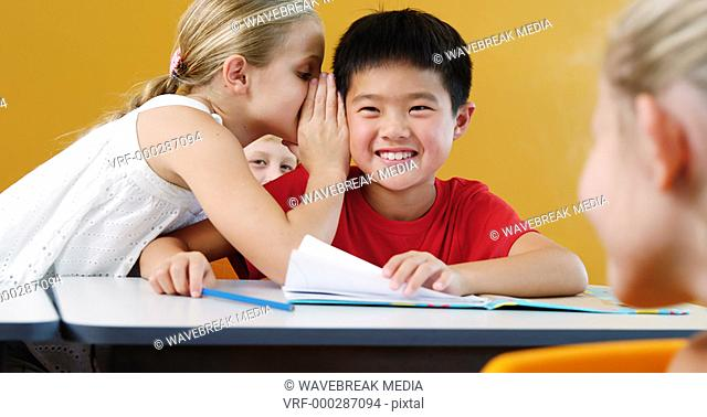 Schoolgirl whispering into his friend s ear in classroom