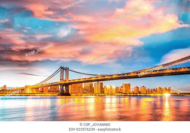 Amazing sunset view of Manhattan Bridge with East River reflecti