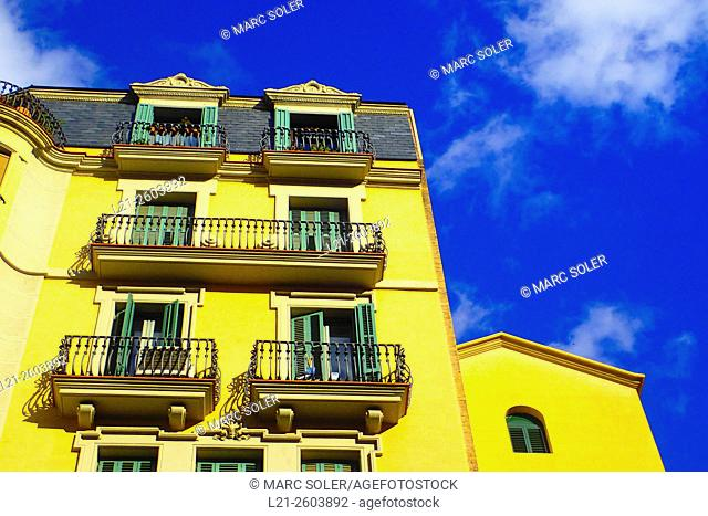 Yellow apartment building, blue sky with white clouds. Barcelona, Catalonia, Spain