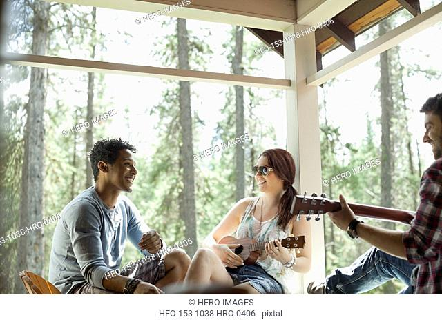 Friends playing music on cabin patio