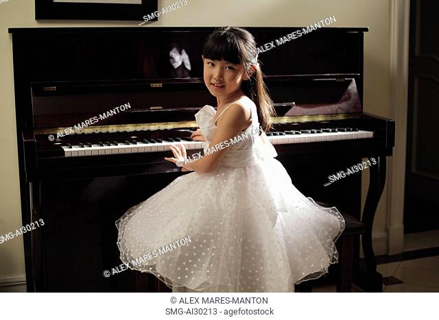 Young girl playing piano in white dress