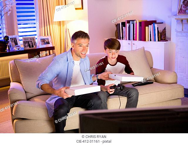 Father and son eating pizza and playing video game in living room
