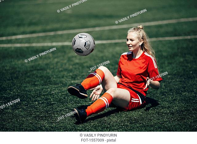 Confident soccer player playing with ball on field