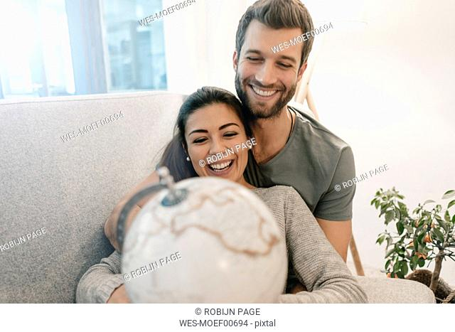 Happy couple on couch at home looking at globe