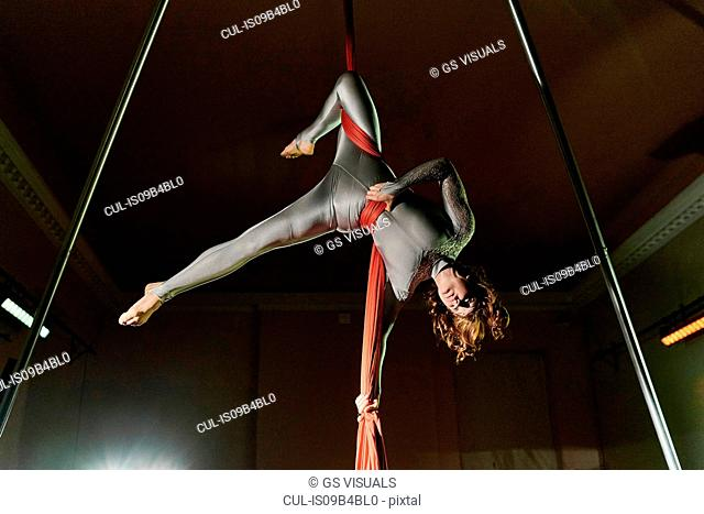 Young female aerial acrobat wrapped upside down in silk rope
