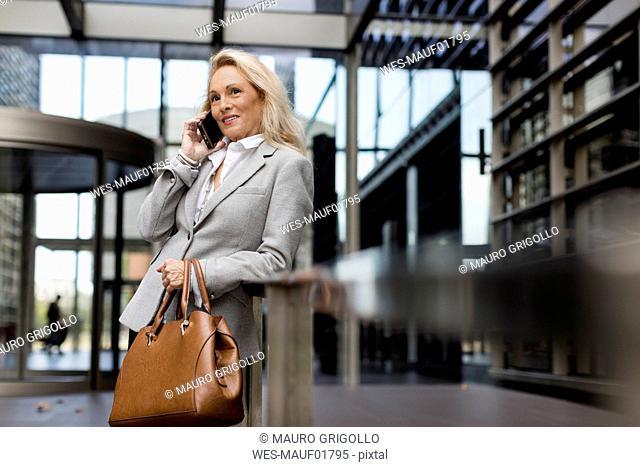 Smiling senior businesswoman talking on cell phone in foyer