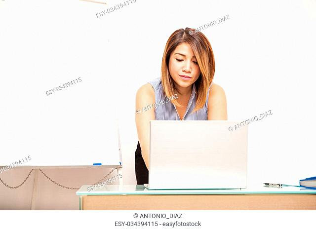 Pretty young businesswoman using a laptop computer and setting up a presentation at an office