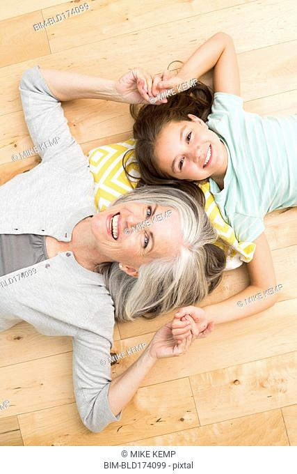 Caucasian grandmother and granddaughter laying on floor