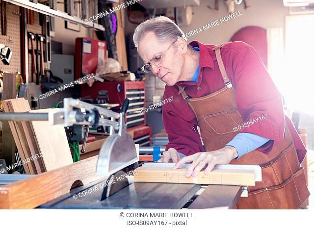 Senior man sawing woodblock in carpentry workshop