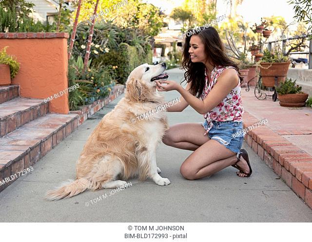 Mixed race woman petting dog on sidewalk