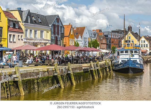 pavement café and fish restaurants at the pier, inner harbour of the coastal town Husum at the North Sea, Germany