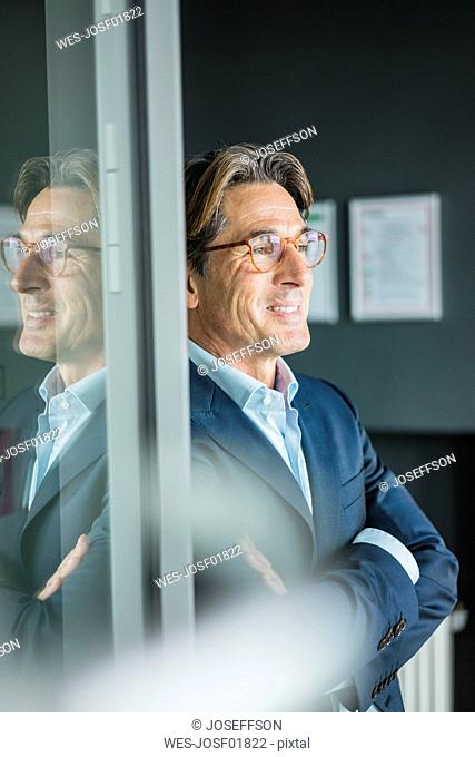 Smiling businessman with glasses in office